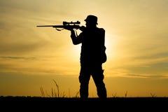 与猎枪的猎人在日落 库存照片