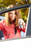 Γυναίκα οδηγών αυτοκινήτων που παρουσιάζει τα νέα κλειδιά αυτοκινήτων και αυτοκίνητο. Στοκ φωτογραφία με δικαίωμα ελεύθερης χρήσης