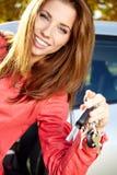 Γυναίκα οδηγών αυτοκινήτων που παρουσιάζει τα νέα κλειδιά αυτοκινήτων και αυτοκίνητο. Στοκ Φωτογραφίες