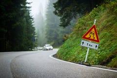 有溜滑路线标志的弯曲的山路和被弄脏的白色汽车在背景中 免版税库存照片