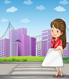 在拿着小配件的高楼前面的一名妇女 免版税库存图片