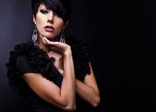 Η όμορφη γυναίκα στο μαύρο κλασσικό φόρεμα θέτει στο στούντιο. Στοκ Φωτογραφία