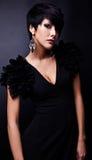 Η όμορφη γυναίκα στο μαύρο κλασσικό φόρεμα θέτει στο στούντιο. Στοκ Φωτογραφίες
