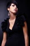 Η όμορφη γυναίκα στο μαύρο κλασσικό φόρεμα θέτει στο στούντιο. Στοκ Εικόνες