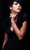Η όμορφη γυναίκα στο μαύρο κλασσικό φόρεμα θέτει στο στούντιο. Στοκ εικόνες με δικαίωμα ελεύθερης χρήσης