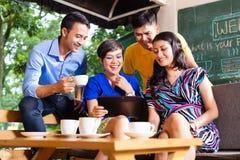 Группа в составе молодые люди в азиатской кофейне Стоковые Изображения RF