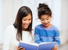 母亲和女儿有书的 免版税图库摄影