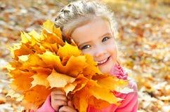 逗人喜爱的微笑的小女孩秋天画象有槭树的离开 免版税库存照片