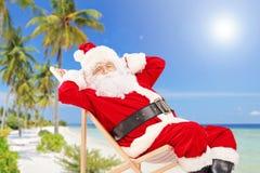 轻松的圣诞老人坐一把椅子,在海滩,享用 库存照片