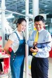 亚裔工头在给训练的纺织品工厂 库存照片