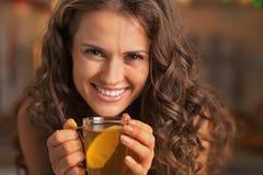 微笑的少妇饮用的姜茶用柠檬 库存图片