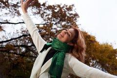 白色毛线衣的美丽的妇女在公园走 免版税库存照片