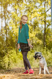 摆在与小狗的嬉戏的小女孩的图象 免版税库存照片