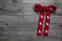 红色编织了与鹿的弓在圣诞节的木背景 免版税库存照片