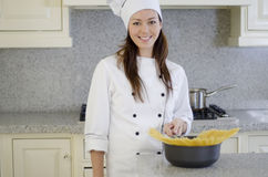 烹调面团的愉快的厨师 免版税库存照片