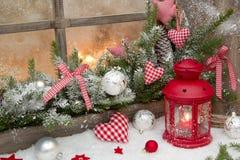 在窗口基石的红色土气圣诞节装饰与被检查的红色 免版税库存照片