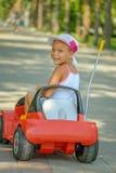 小女孩骑马玩具汽车 免版税图库摄影