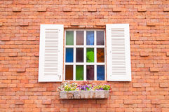 与多颜色玻璃和砖墙的美丽的木窗口 免版税库存照片