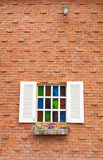 与多颜色玻璃和砖墙的美丽的木窗口 免版税库存图片