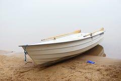 白色小船在岸有薄雾的早晨 免版税库存图片