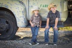 戴牛仔帽的两个年轻男孩倾斜反对古色古香的卡车 库存照片