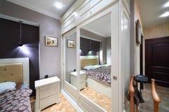 与被反映的门的固定白色衣橱在卧室 免版税库存图片