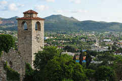在谷和小山的背景的中世纪钟楼 免版税库存照片