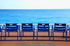 在海江边,尼斯,法国的蓝色空的椅子 库存照片
