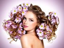Νέα όμορφη γυναίκα με τα λουλούδια στις τρίχες Στοκ Φωτογραφίες