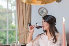喝红葡萄酒的可爱的妇女 库存图片