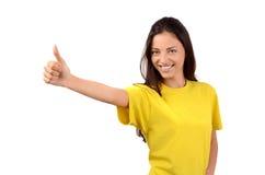 Το ευτυχές κορίτσι με την κίτρινη υπογραφή μπλουζών φυλλομετρεί επάνω. Στοκ φωτογραφίες με δικαίωμα ελεύθερης χρήσης