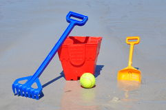 红色桶锹球和犁耙在海滩 免版税图库摄影
