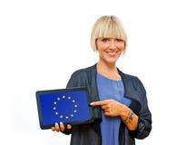 拿着有欧盟旗子的可爱的白肤金发的妇女片剂 免版税图库摄影