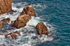 Πέτρες στο μπλε θάλασσας βαθιά με τα κύματα Στοκ Εικόνες