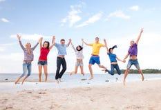 跳跃在海滩的小组朋友 库存照片