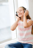 有耳机的小女孩在家 图库摄影