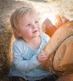 有牛仔帽的可爱的女婴在南瓜补丁 免版税库存照片