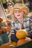 牛仔帽的小男孩在南瓜补丁 库存照片