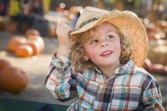牛仔帽的英俊的小男孩在南瓜补丁 库存图片