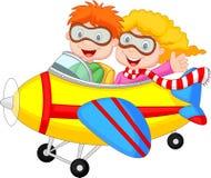 逗人喜爱的动画片男孩和女孩在飞机上 图库摄影