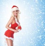 一个年轻和性感的白肤金发的开头圣诞节礼物 库存照片