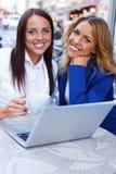咖啡馆的两个美丽的女孩与膝上型计算机 免版税库存照片