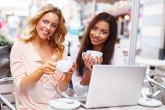 咖啡馆的两个美丽的女孩与膝上型计算机 免版税图库摄影