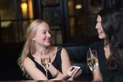使用手机,两个妇女朋友在夜 免版税库存照片