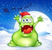 戴一个红色圣诞老人帽子的一个肥胖绿色妖怪 免版税库存照片