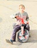 摩托车的咧嘴笑的男孩 免版税库存照片