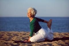 做瑜伽的资深妇女由海洋 免版税库存图片