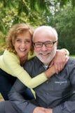 一起笑一对资深的夫妇的画象户外 免版税库存图片