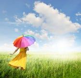 Όμορφη γυναίκα που κρατά την πολύχρωμη ομπρέλα στον πράσινους τομέα χλόης και τον ουρανό σύννεφων Στοκ Εικόνα