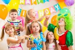 与庆祝生日聚会的小丑的快活的孩子 免版税库存照片